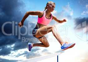 Athlete jumping over a hurdle against sky in background