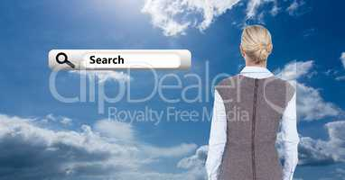 Rear view of business woman looking at search bar icon against cloudy sky
