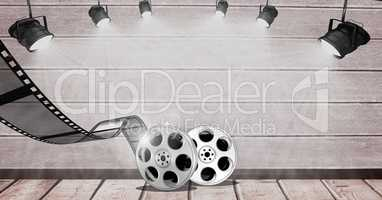 Film reel against spot lights on wooden background