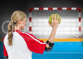 Female athlete throwing handball against goal post in background