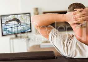 Rear view of man sitting on sofa watching sport channel on tv in living room