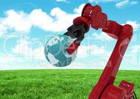 Red robot claw holding globe against green grass field and sky