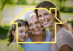 Mother, daughter and grandmother smiling together in the park with house outline