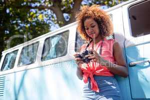 Woman leaning on campervan and checking photo on camera