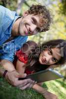 Couple lying on grass and using digital tablet
