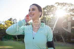Smiling female jogger with headphones taking a break from exercise