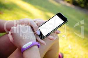 Woman with fitness band on her wrist using her mobile phone