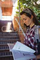 Attentive schoolgirl reading book near staircase