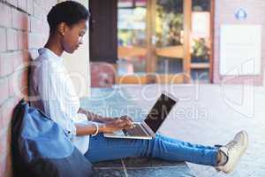 Attentive schoolgirl sitting against brick wall and using laptop