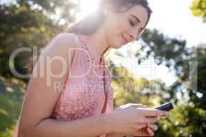 Beautiful woman using her mobile phone in the park