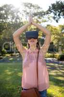 Woman standing with her hands joint while using a VR headset in the park