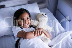 Portrait of patient relaxing on bed with teddy bear