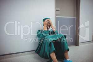 Tensed female surgeon sitting in corridor