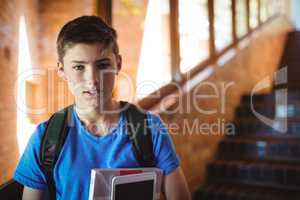 Portrait of schoolboy holding digital tablet and book near staircase