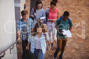 Students holding books and digital tablet walking in school campus
