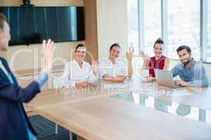 Business executives waving hands to colleague in conference room