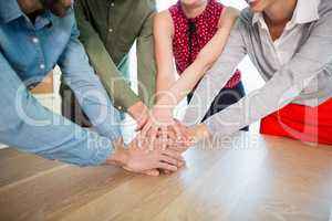 Business executives with their hands stacked on wooden table