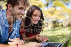 Couple lying on grass and using laptop
