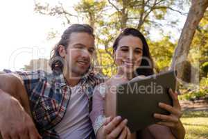 Couple sitting on grass and using digital tablet