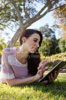 Woman lying on grass and using digital tablet