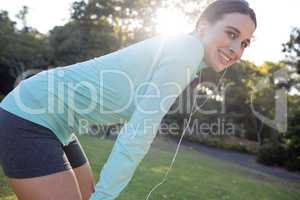 Smiling female jogger listening to music and leaning on knees while exercising