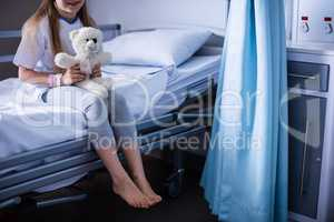 Patient sitting with teddy bear on hospital bed