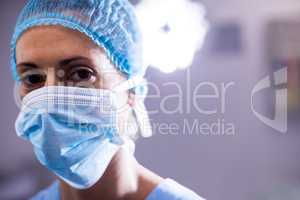 Portrait of female nurse wearing surgical mask in operation theater