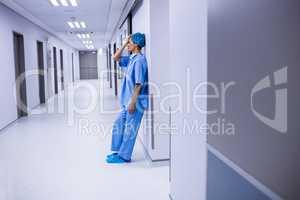 Sad surgeon leaning on wall in corridor
