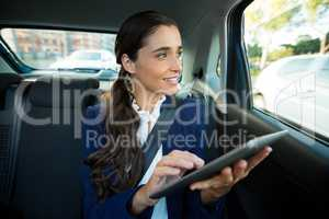 Business executive using digital tablet in car