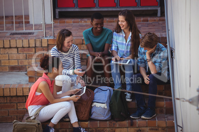 Students using digital tablet on staircase