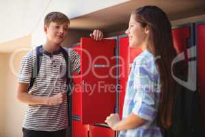 Happy students interacting with each other in locker room