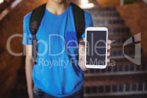 Schoolboy standing with schoolbag showing mobile phone near staircase at school