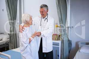 Doctor assisting senior patient in ward