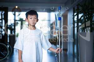 Boy patient holding intravenous iv drip stand in corridor