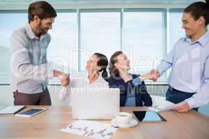 Smiling business executives shaking hands with each other in conference room