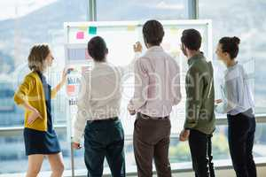 Group of business executives looking at white board