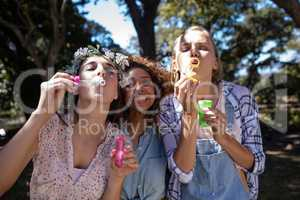 Female friends blowing bubbles in park