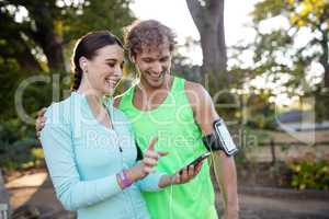 Couple looking at smartphone while jogging