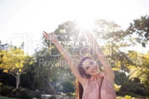 Happy woman standing in the park with her hands raised