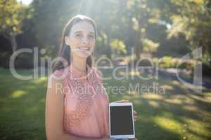 Portrait of a smiling woman holding a digital tablet in the park