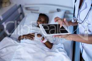 Female doctor using digital tablet during visit in ward