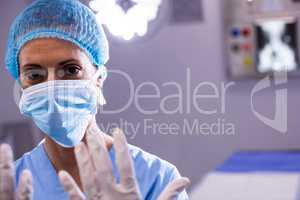 Portrait of female surgeon preparing for operation in operation room