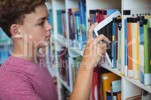 Student keeping digital tablet in bookshelf in library