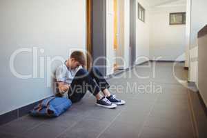 Sad schoolboy sitting in corridor
