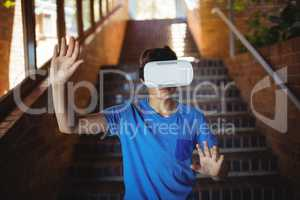 Schoolboy using virtual reality headset on staircase