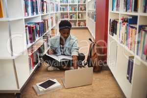 Schoolgirl sitting on floor and doing homework in library