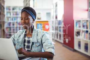 Schoolgirl using laptop in library