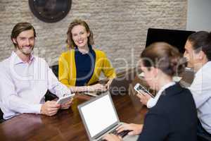 Business executives smiling while using electronic devices on conference table