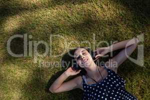 Woman lying on grass and listening to music with headphones