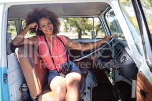 Woman sitting at driver's seat of campervan with camera